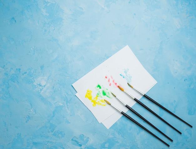 Buntes beflecktes zeichenpapier mit pinsel auf blauem hintergrund