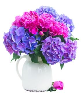 Buntes blumenstrauß der hellen rosa pfingstrose, der eustoma und der blauen hortensia in der vase lokalisiert auf weiß