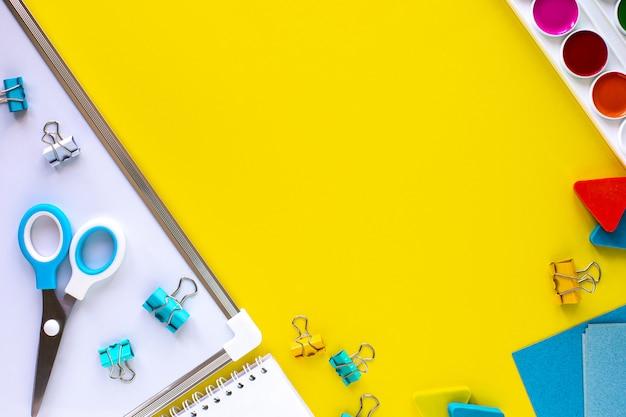 Buntes briefpapier der schule auf gelbem hintergrund mit copyspace.