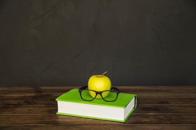 Buntes buch mit gläsern und apfel auf schreibtisch