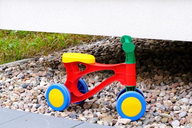 Buntes dreirad der kinderplastik auf einem kies in einem spielplatz im hof am sommertag.