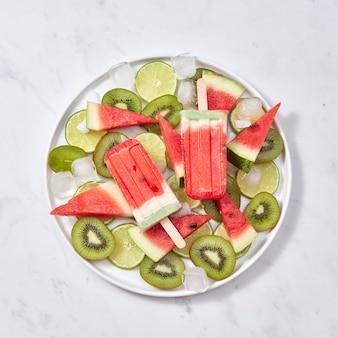Buntes eisiges eis am stiel. appetitliches hausgemachtes wassermeloneneis in einem teller mit limetten-, wassermelonen-, kiwi- und eiswürfelscheiben auf einem grauen marmortisch mit einer kopie des raumes. flach liegen