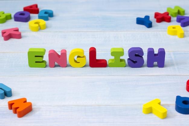 Buntes englisches wort hölzern auf blauem hölzernem hintergrund. englisch sprachlernkonzept