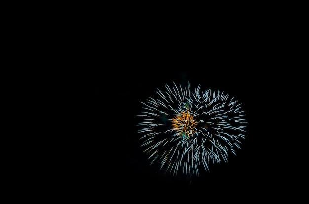 Buntes feuerwerk auf dem schwarzen himmel hintergrund über dem wasser