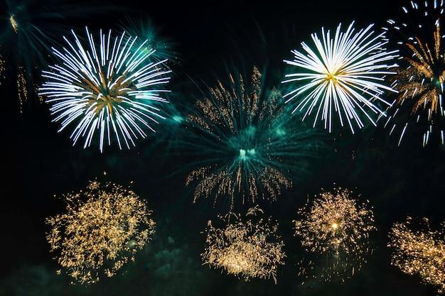 Buntes feuerwerk der vielfalt auf dem nachthimmelhintergrund. gruß mit gelben und blauen blitzen.