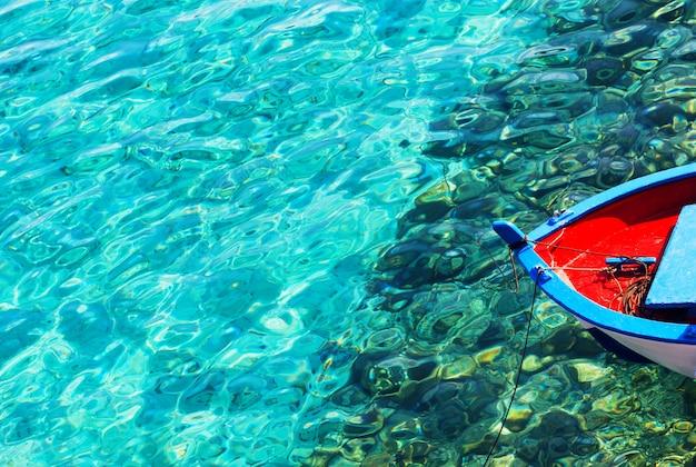 Buntes fischerboot auf einem klaren blauen wasser an einem sonnigen tag. abstrakter hintergrund mit exemplarplatz.