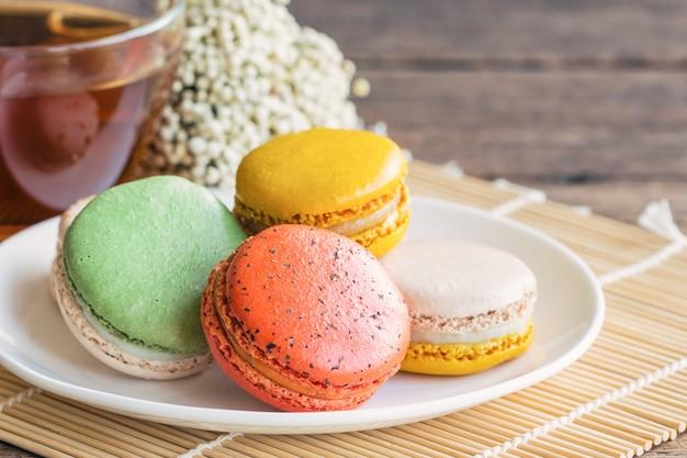 Buntes französisches macaron oder italienisches macaron auf weißer platte diente mit tee oder kaffee.