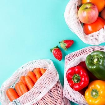 Buntes frisches obst und gemüse in wiederverwendbaren baumwollbeuteln auf blauem hintergrund. zero waste oder verantwortungsvolles einkaufs- und lagerkonzept für lebensmittel. nachhaltiger lebensstil