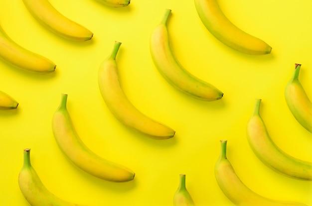 Buntes fruchtmuster. bananen über gelbem hintergrund. ansicht von oben. pop-art-design, kreatives sommerkonzept. minimaler, flacher laienstil.