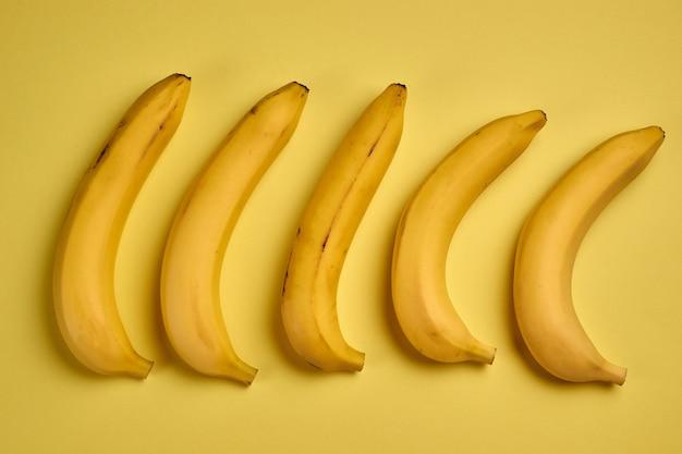 Buntes fruchtmuster der frischen gelben bananen auf gelb