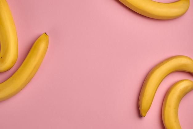 Buntes fruchtmuster der frischen gelben bananen auf rosa