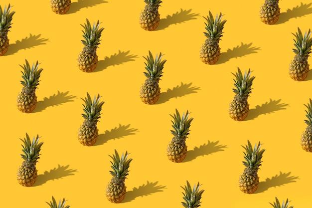 Buntes fruchtmuster des sommers von frischen ananas auf gelb mit schatten