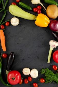 Buntes gemüse frisches gemüse wie gelbe paprika und andere auf grauem schreibtisch