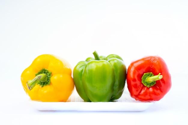 Buntes gemüse, gelb, grün und rot, paprika auf schaumstoffschale lokalisiert auf weißem hintergrund