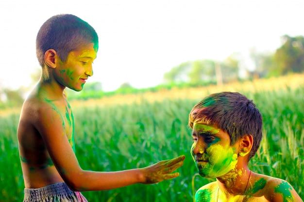 Buntes gesicht des indischen kindes im holi festival
