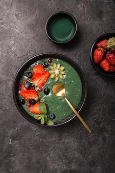 Buntes, gesundes essen. acai smoothie schüssel. keto frühstück idee. fruchtquark smoothie, acai. frühstück mit grüner spirulina, erdbeere, chia, kiwi auf schwarzem teller