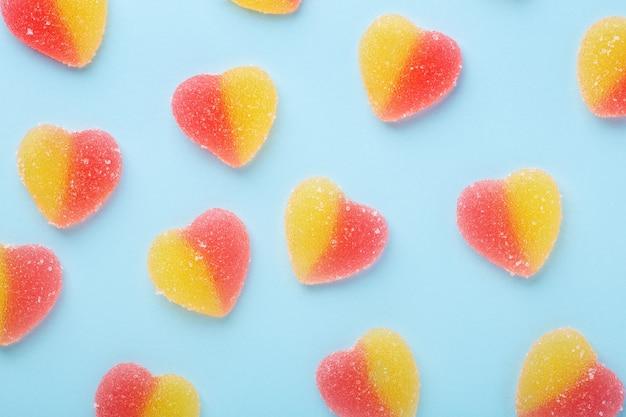 Buntes gummibärchenmuster auf blauem tisch. gelee süßigkeiten in form des herzens.