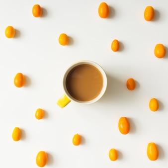 Buntes helles muster aus kumquatfrucht mit kaffeetasse. flach liegen.