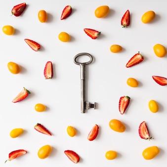 Buntes helles muster aus kumquatfrucht und erdbeeren mit vintage-schlüssel. flach liegen.