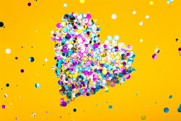 Buntes herz gemacht von den konfettis auf gelbem hintergrund