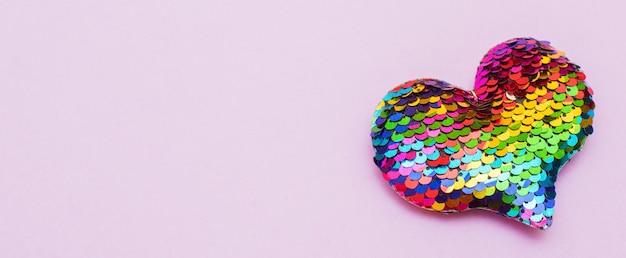 Buntes herz gemacht von pailletten auf einem rosa hintergrund