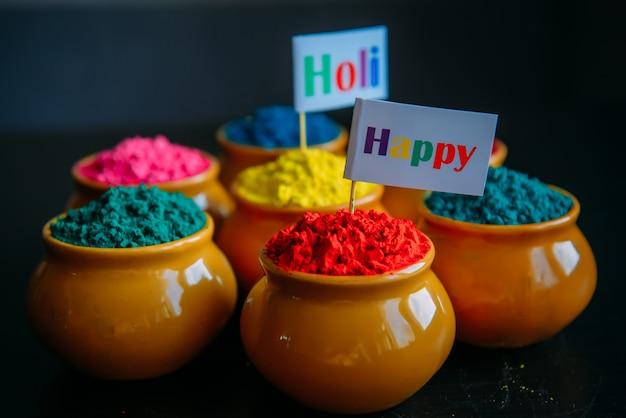 Buntes holipulver in der tasse nahaufnahme. helle farben für das indische holi-festival im kreis der tontöpfe. selektiver fokus. schwarzer hintergrund