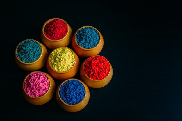 Buntes holipulver in der tasse nahaufnahme. helle farben für das indische holi-festival in tontöpfen. selektiver fokus. schwarzer hintergrund, draufsicht