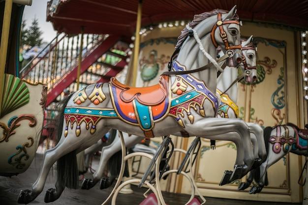 Buntes karussellpferd auf einem beleuchteten vintage-kreisverkehrskarussell