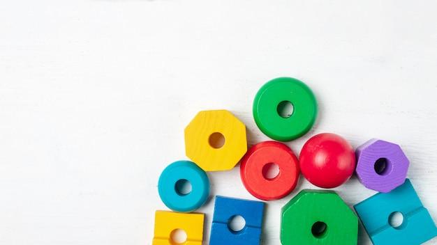 Buntes kinderspielzeug auf weißem holz. draufsicht. flach liegen. kopieren sie platz für text