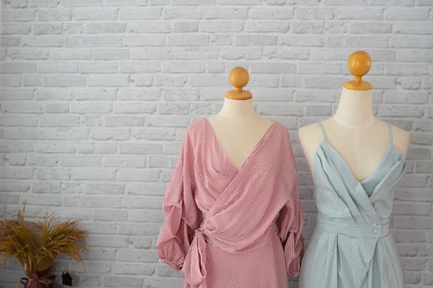 Buntes kleid auf weißem backsteinmauerbeschaffenheitshintergrund in der umkleidekabine.