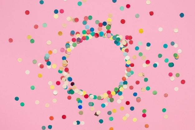 Buntes konfetti aus papier in einem kreis auf rosa isolierter oberfläche ausgebreitet
