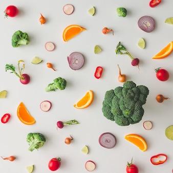 Buntes lebensmittelmuster aus brokkoli, orange, rotem pfeffer, zwiebeln, tomaten und limette