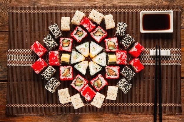 Buntes leckeres sushi serviert auf brauner strohmatte, flach. essenskunst, schöne verzierung. japanische küche, restaurantmenüfoto.