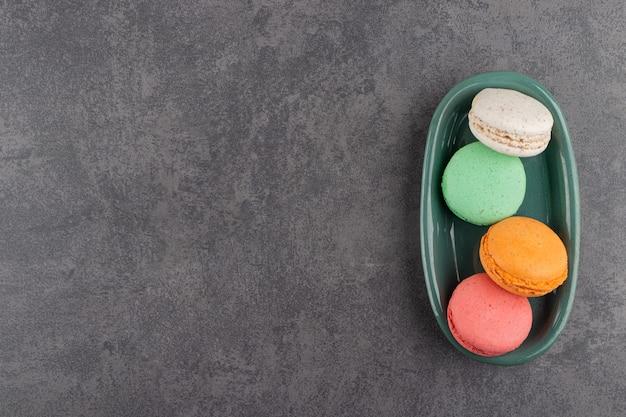 Buntes macarons-dessert, das auf einen steintisch gelegt wird.