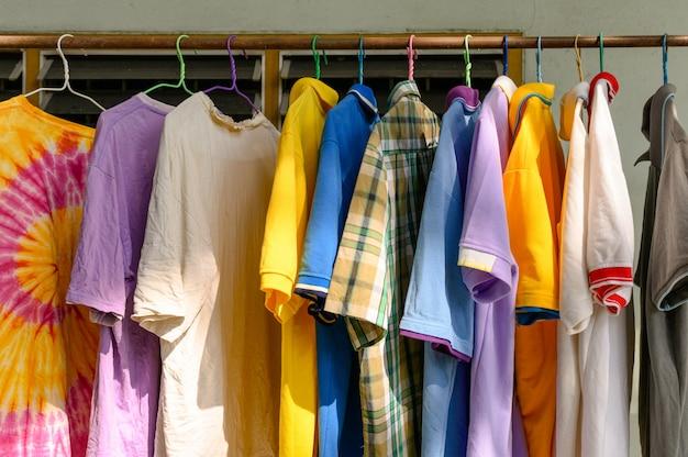 Buntes männliches hemd, das an der wäscheleine in sonnigem hängt