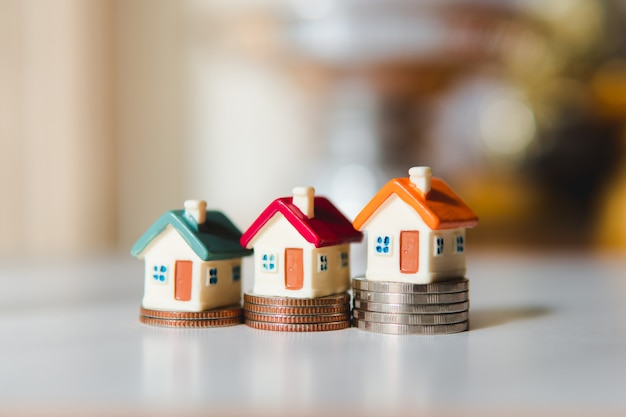 Buntes miniaturhaus auf stapelmünzen unter verwendung als eigentum und finanzkonzept