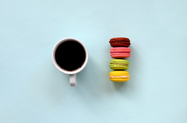 Buntes nachtischkuchen macaron oder makronen- und kaffeetasse auf draufsicht des modischen blauen pastellhintergrundes