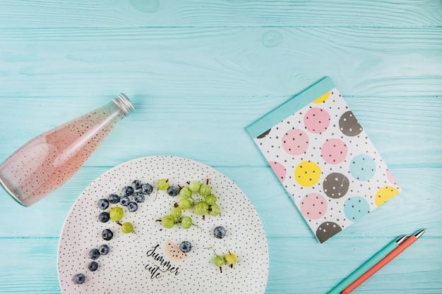 Buntes notizbuch und stifte mit früchten auf einem blauen hintergrund