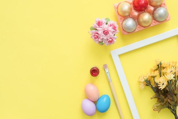 Buntes osterei der draufsicht der draufsicht legen gemalt in der pastellfarbzusammensetzung und in den frühlingsblumen