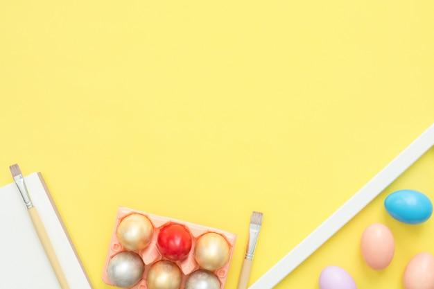 Buntes osterei der draufsicht der ebene legen gemalt in der pastellfarbzusammensetzung mit pinsel auf gelb