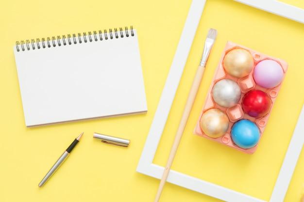 Buntes osterei der draufsicht der ebene legen gemalt in der pastellfarbzusammensetzung und verspotten herauf leeres notizbuch