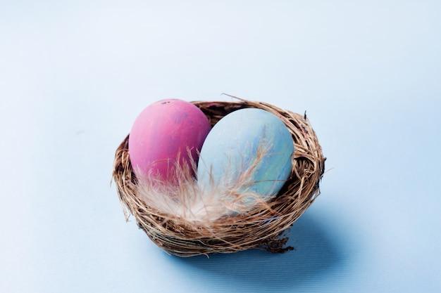 Buntes osterei im nest auf blauem hintergrund mit kopienraum. ostern hintergrund minimalismus