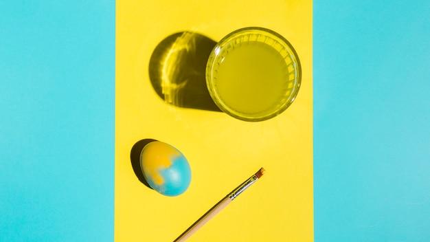 Buntes osterei mit pinsel und glas wasser