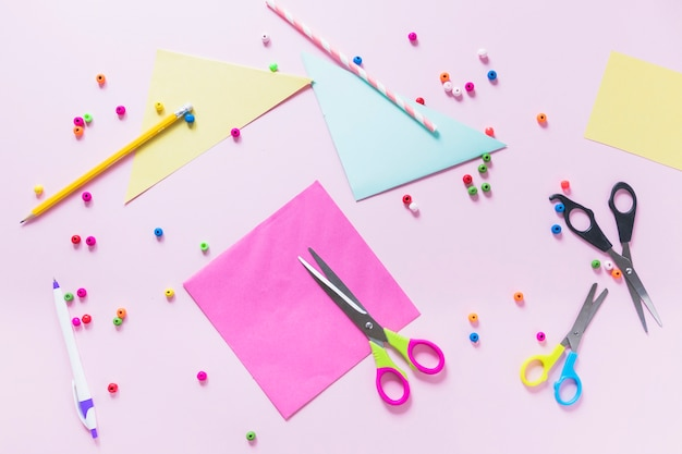 Buntes papier; bleistift; stift; perlen und schere auf rosa hintergrund