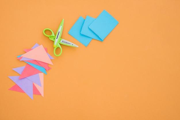 Buntes papier und schere auf farbigem hintergrund