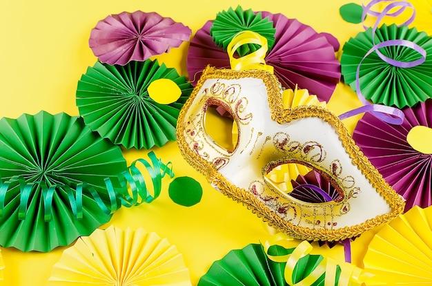 Buntes papierkonfetti, karnevalsmaske und farbiger serpentin auf gelbem grund