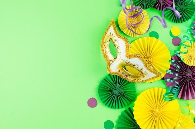 Buntes papierkonfetti, karnevalsmaske und farbiger serpentin auf grünem hintergrund