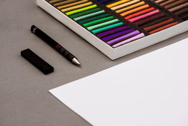 Buntes pastell, stift, papier auf grauem tisch