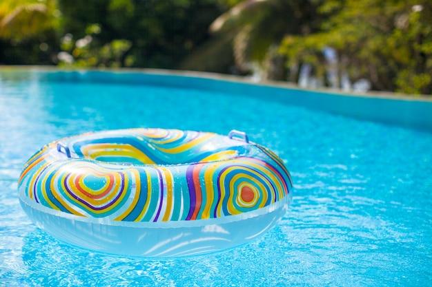 Buntes poolfloss im blauen schwimmbecken