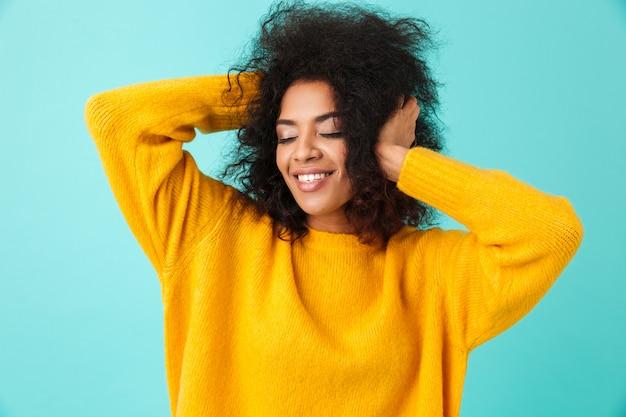 Buntes porträt der entzückenden frau im gelben hemd, das ihr dunkles lockiges haar aufwirft und berührt, lokalisiert über blauer wand